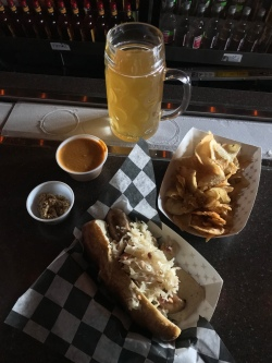 Mug of beer on frosty rail, homemade chips, bratwurst on pretzel bun with sauerkraut, whole-grain mustard and beer cheese on the side