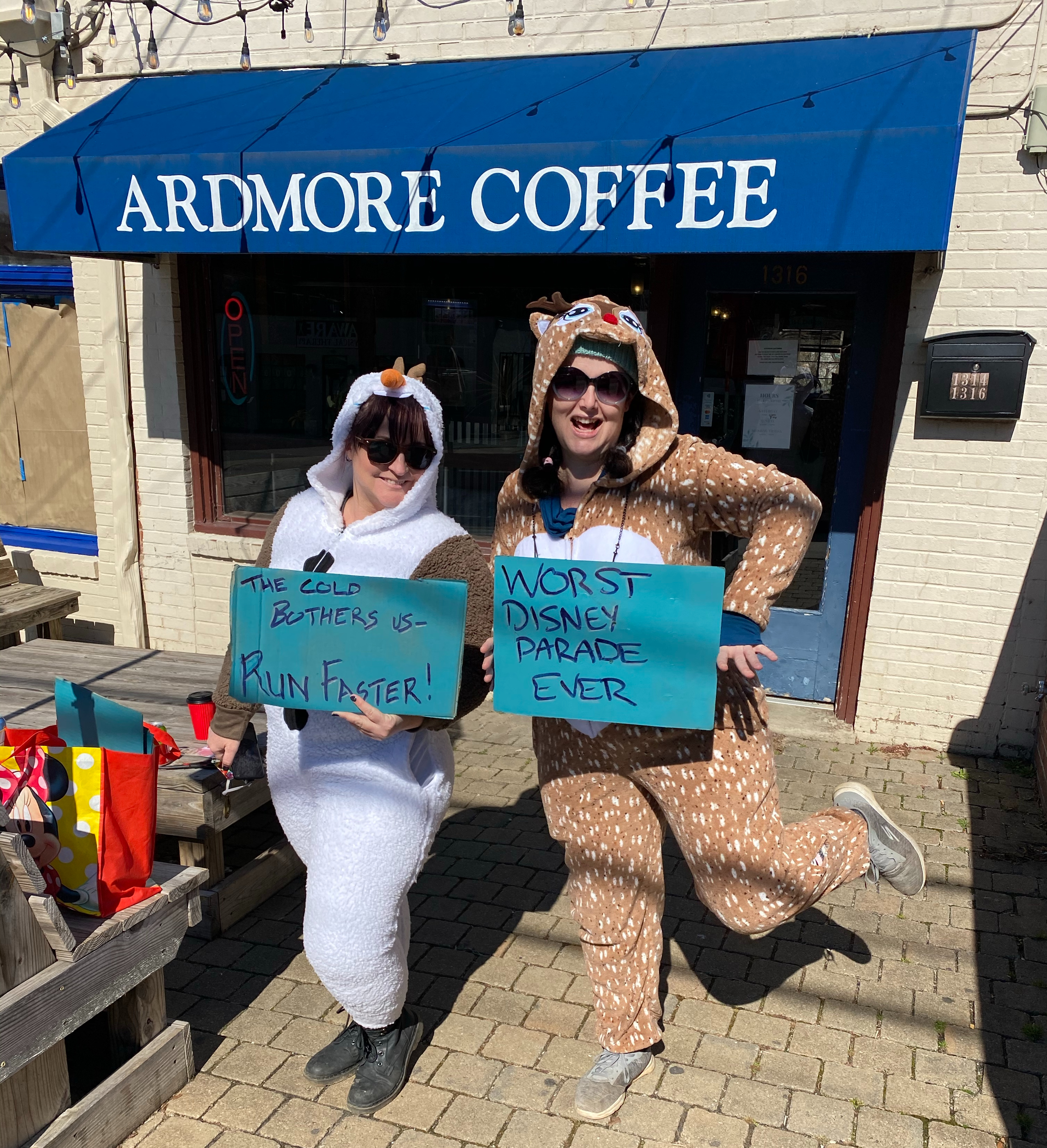"Women in Olaf and reindeer onesies outside a coffee shop. Olaf holds a sign saying ""the cold bothers us, run faster"", the deer's sign says ""worst Disney parade ever""."